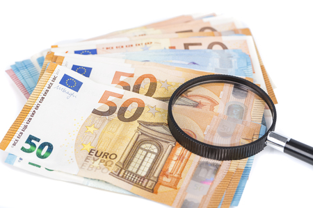 magnifying glass and pile of euro notes on white background Stock Photo