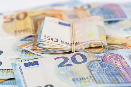 Wad of euro bills banknotes cash on table.