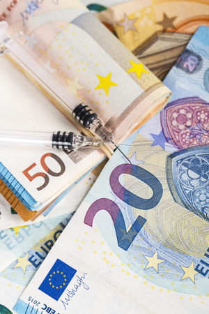 Syringes and wad of euros banknotes bills cash. Cost of health, medicine, drug. Close-up.