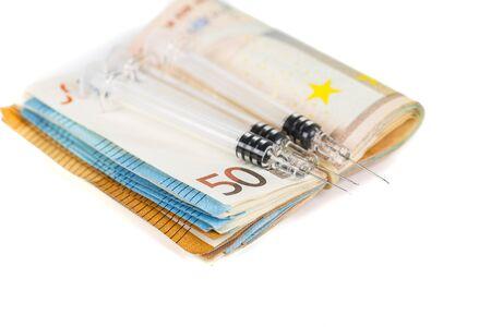 expensive: Syringes and wad of euros banknotes bills cash. Cost of health, medicine, drug. Close-up.