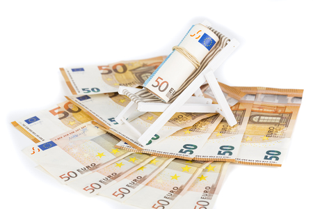 Rolled Up Bundle Of Fifty euro Banknotes bills, On Miniature Deck Chair sun lounger. Concpet of prices, costs of holiday, travel. Stock Photo
