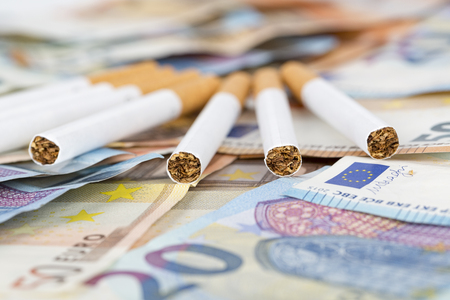 20 and 50 Euro banknotes bills cash with cigarettes. Concept of cost of tabacco, cigarettes. Front and top view, close-up.