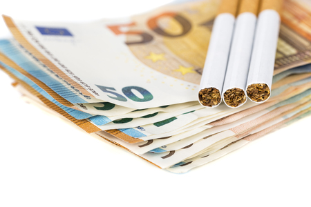 expensive: 20 and 50 Euro banknotes bills cash with cigarettes, with cigarettes box. Concept of cost of tabacco, cigarettes. Front and top view, close-up. On white background