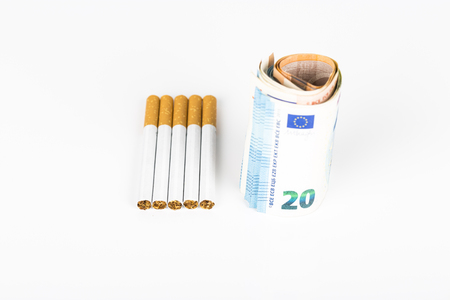 one hundred dollars: Euro banknotes wrapped, rolled up, winded, with cigarettes on the white table. Concept of the prices, cost of cigarettes tabacco Stock Photo