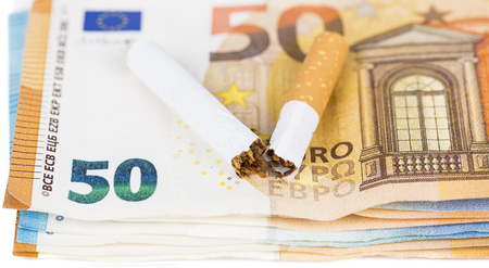 expensive: Cigarette broken on euro banknotes. Concept of waste of health and money lost due to smoking addiction - Stopping smoking