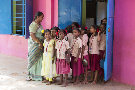 PONDICHERY, PUDUCHERY, INDIA - SEPTEMBER 04, 2017. Unidentified boys children teacher go out from the classroom with their plates to have a lunch at the outdoor canteen.