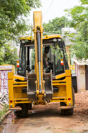 PONDICHERY, PUDUCHERY, INDIA - SEPTEMBER 03, 2017. yellow bulldozer, tractor with a bucket , back view ready to work