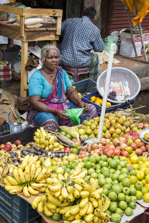 PONDICHERY, PUDUCHERY, INDIA - SEPTEMBER 09, 2017. Unidentified man woman at his fruit and or vegetables shop in the main market of the city, in south of India, Asia. Editorial