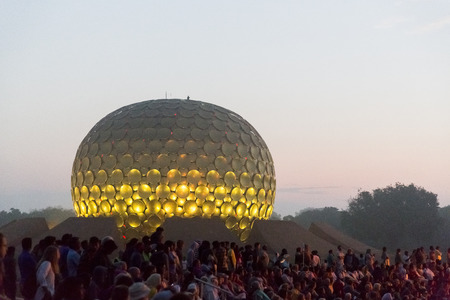 AUROVILLE, TAMIL NADU, INDIA - February 28, 2018. Collective Meditation with dawn fire. On Auroville's 50 years Birthday, at the Matrimandir Amphitheater Stock Photo - 120015535