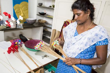 PUDUCHERY, PONDICHERY, TAMIL NADU, INDIA - March circa, 2018. Unidentified female women man artist make jeweleries paper and flowers paper by hand.