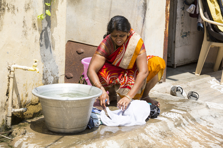 PUDUCHERY, PONDICHERY, TAMIL NADU, INDIA - March circa, 2018. Unidentified indian woman wash laundry clothes outdoors. India
