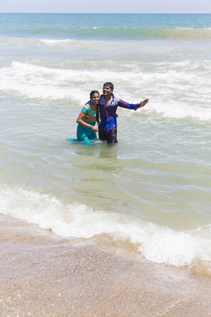 MASI MAGAM FESTIVAL, PUDUCHERY, PONDICHERY, TAMIL NADU, INDIA - March 1, 2018. Unidentified Indian pilgrims young couple bathing, in the sea, on the beach. Love and complicity feeling