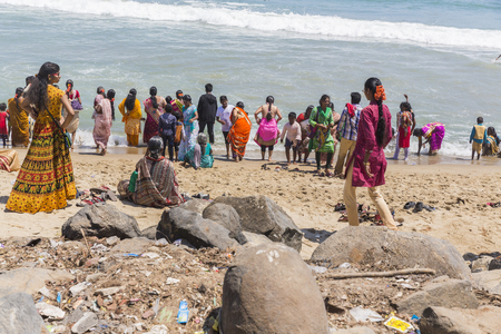 MASI MAGAM FESTIVAL, PUDUCHERY, PONDICHERY, TAMIL NADU, INDIA - March 1, 2018. Group of unidentified Indian pilgrims women men bathing in the sea, on the beach