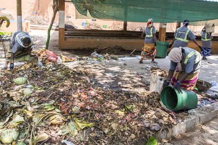 PUDUCHERY, PONDICHERY, TAMIL NADU, INDIA - March circa, 2018. Indian women are sorting waste in garbage dumps to recycle. With gloves ans masks for hygienic