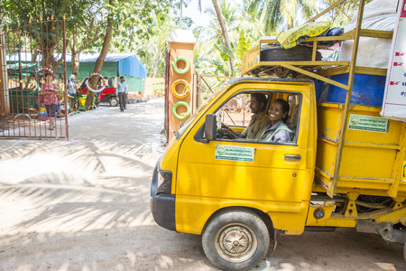 PUDUCHERY, PONDICHERY, TAMIL NADU, INDIA - March circa, 2018. Small yellow garbage truck with people, back to the recycling center Editorial