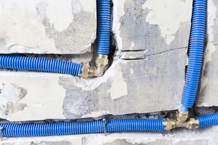 Water pipes made of polypropylene PEX in the wall, plumbing in the house. Installation of sewer pipes in a bathroom of an apartment interior during renovation works. Blue plastic drain pipe for used water