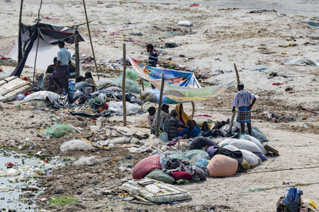 Documentary editorial. RAMESWARAM, RAMESHWARAM, PAMBAN ISLAND, TAMIL NADU, INDIA - March circa, 2018. Unidentified poor local Traditional fisherman are living on the beach in the middle of the garbage and cows and goats, under tents made with cloths. Asia Editorial