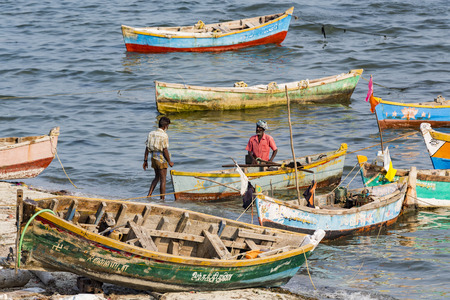 Documentary editorial. RAMESWARAM, RAMESHWARAM, PAMBAN ISLAND, TAMIL NADU, INDIA - March circa, 2018. Unidentified poor local Traditional fisherman are fishing on the beach with very small colored wood boats. Asia