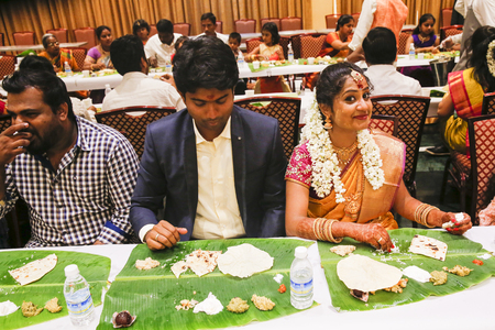 PUDUCHERY, PONDICHERY, TAMIL NADU, INDIA - SEPTEMBER CIRCA, 2017. Unidentified Indian bride and groom and guest, at table for lunch. Food on leaf, traditional dinner for wedding. Editorial