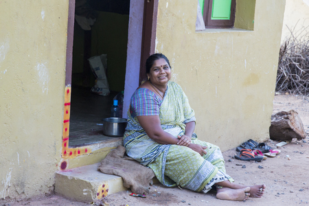 PUDUCHERRY, PONDICHERY, TAMIL NADU, INDIA - SEPTEMBER CIRCA, 2017. An unidentified Indian woman sitting on the sidewalk in front of her house. Editorial