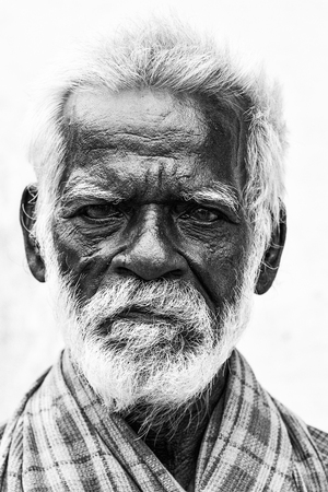 PONDICHERY, PUDUCHERRY, TAMIL NADU, INDIA - SEPTEMBER CIRCA, 2017. An unidentifed old senior indian poor man portrait with a dark brown wrinkled face and white hair and a white beard, looks serious or sad. Black and white