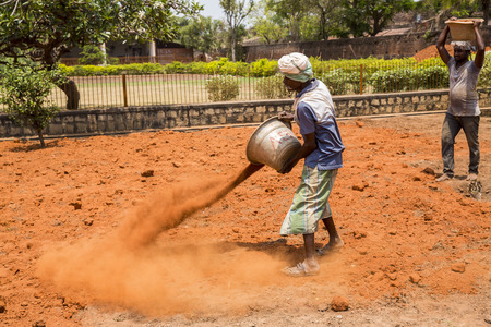 PONDICHERY, PUDUCHERRY, TAMIL NADU, INDIA - SEPTEMBER CIRCA, 2017. Unidentified Indian men at work with seal to move the orange ocher tan earth to cultivate food vegetables grass