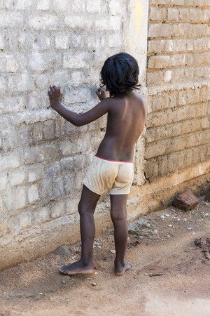 PONDICHERY, PUDUCHERRY, TAMIL NADU, INDIA - March circa, 2018. Unidentified Small indian barefoot boy in worn out poor clothes playing with the wall in the street