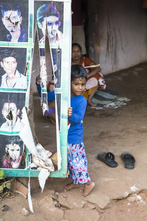 PONDICHERY, PUDUCHERRY, TAMIL NADU, INDIA - SEPTEMBER circa, 2018. An unidentified poor indian boy with a smiling and serious eyes looks in the camera 報道画像