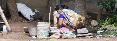 PONDICHERY, PUDUCHERRY, TAMIL NADU, INDIA - SEPTEMBER CIRCA, 2017. Unidentified Indian poor woman wash clothes in street rural village
