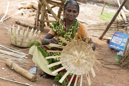PONDICHERY, PUDUCHERRY, TAMIL NADU, INDIA - SEPTEMBER CIRCA, 2017. the portrait of an unidentified woman make local wicker basket. handcraft and handmade for local concept. With smile