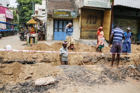 PONDICHERY, PUDUCHERY, INDIA - SEPTEMBER 04, 2017. Unidentified workers with shovels in a trench, dig trenches along the road. Concept of hard work in construction