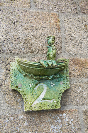Close-up of a house number made with terracotta with creative design.