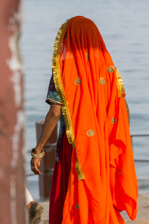 Portrait of Asian senior beautiful woman wearing traditional orange Indian dress sari. Near the beach, from behind. India Stock Photo
