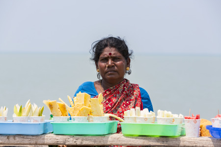 RAMESHWARAM, TAMIL NADU, INDIA - MARCH CIRCA, 2018. Unidentified Indian trader woman in her shop on local market selling all kind of goods, fuits, vegetables