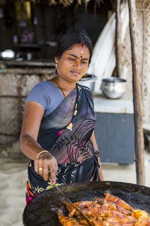 RAMESHWARAM, TAMIL NADU, INDIA - MARCH CIRCA, 2018. Unidentified woman cooking fresh fish on the grill barbecue in the restaurant
