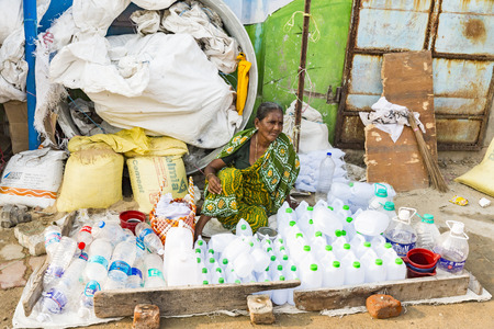 RAMESHWARAM, TAMIL NADU, INDIA - MARCH CIRCA, 2018. Unidentified Indian trader woman in her shop on local market selling plastic bottles