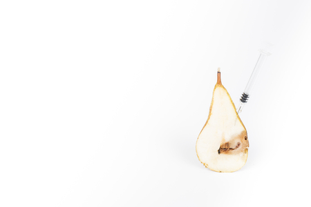 Close-up Boring trace of a codling moth Cydia Pomonella, in a half middle wormy pear. On white background. With syringe needle. Concept non organic food and genetically modified organism. Place to write