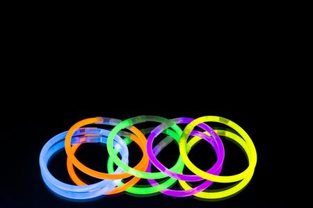 Colorful fluorescent light neon glow stick bracelet strap wristband on mirror reflection black background. Yellow Blue pink orange green violet glow sticks 写真素材