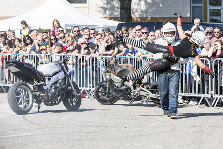 LE TRAIT, SEINE MARITIME, NORMANDY, FRANCE - SEPEMBER 01, 2018. Moto-show in central square of city. Tricks on ATV stuntmen, Stunt Riding - Wheelie, Stoppie and extreme acrobatics somersault on motorbike with a woman. Outdoor spectacle Éditoriale