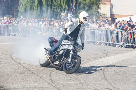 LE TRAIT, SEINE MARITIME, NORMANDY, FRANCE - SEPTEMBER 01, 2018. Moto-show in central square of city. Tricks on ATV stuntmen, Stunt Riding - Wheelie, slides, sliding, Stoppie and extreme acrobatics somersault on motorbike