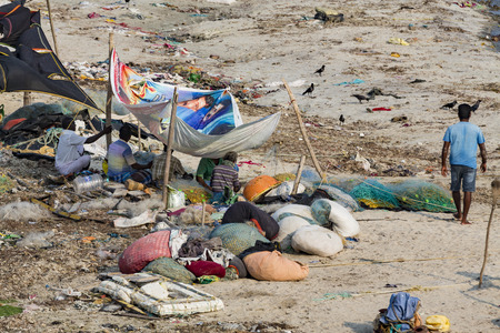 RAMESWARAM, RAMESHWARAM, PAMBAN ISLAND, TAMIL NADU, INDIA - March circa, 2018. Unidentified poor local Traditional fisherman are living on the beach in the middle of the garbage and cows and goats, under tents made with cloths.