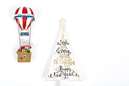 Santa Claus in Hot air balloon flight up to a wood white tree with Merry Christmas Happy new year written on, on white background. Place to write