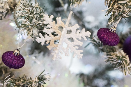 Close up shot of a christmas tree with beautiful decoration. Colorful purple balls decoration hanging on a christmas tree. with snow