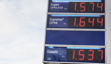 Blue board with prices of gas petroleum, written in red. Oil petrol energy in Europ, France, Euro. Outdoor. Morning light summer tone. Concept finance inflation prices