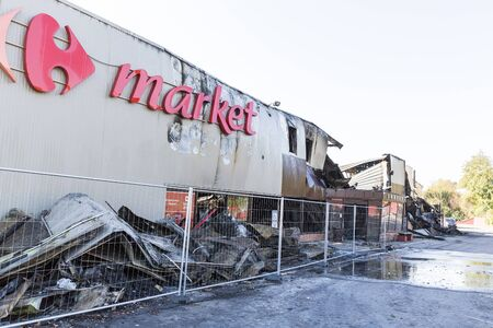 DUCLAIR, FRANCE - OCTOBER Circa, 2018 : Damaged CARREFOUR MARKET supermarket after arson fire with burn debris of twisted metallic structure after intense burning waiting for investigation insurance