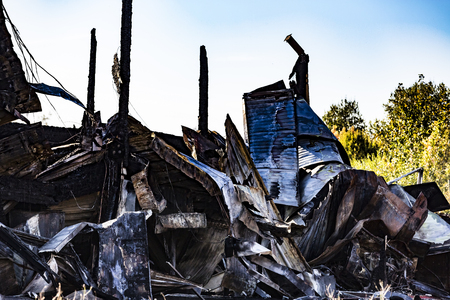 Damaged industry supermarket after arson fire with burn debris of twisted metallic wood structure after intense burning fire disaster ruins waiting for investigation for insurance. Saturated contrasting colors effect dramatic atmosphere Imagens