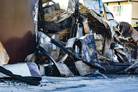 Damaged industry supermarket after arson fire with burn debris of twisted metallic wood structure after intense burning fire disaster ruins waiting for investigation for insurance. Saturated contrasting colors effect dramatic atmosphere Reklamní fotografie
