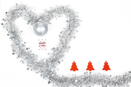 Christmas silver grey garland decoration photo as a heart for love emtion with a Merry Christmas label and red paper trees on white background.