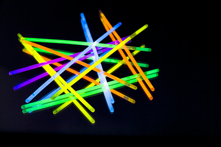 Colorful fluorescent light neon glow stick on mirror reflection black background. Yellow Blue pink orange green violet glow sticks