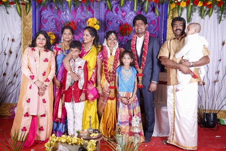 PONDICHERY, PUDUCHERY, TAMIL NADU, INDIA - SEPTEMBER CIRCA, 2017. Beautiful Indian newlyweds stands with their bridesmaids and groomsmen and family, dressed in saris, sherwanis, lehengas outside and look cheerful Editorial